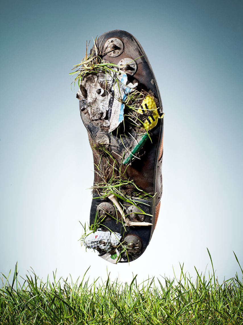 golf shoe bottom with golf items stuck on spikes conceptual photography michael nieland